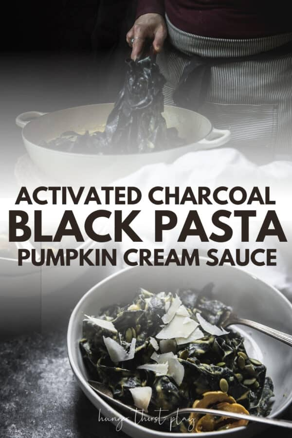 overhead angle of charcoal pasta in a bowl with cream sauce and shved parmesan