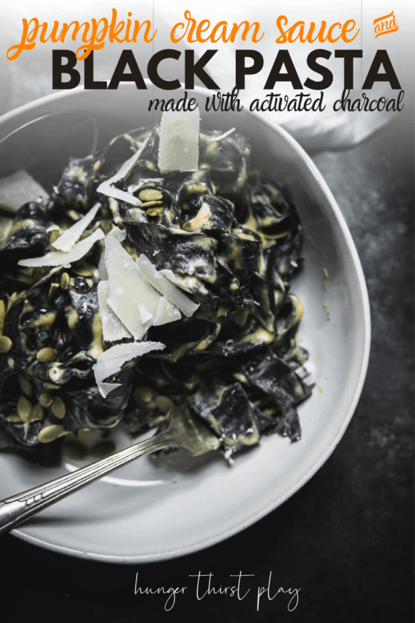 close up of black pasta with cream sauce and shaved parmesan in a bowl with utensils