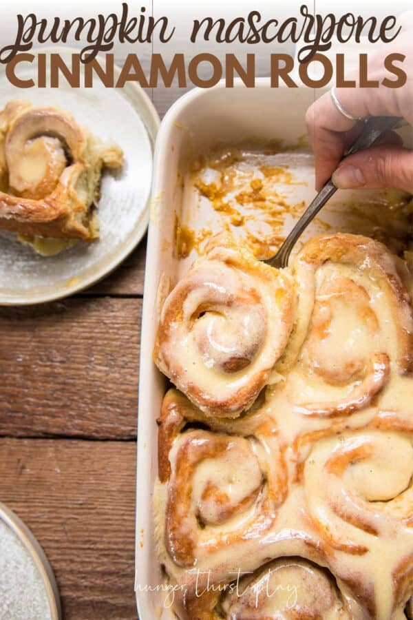 scooping a cinnamon roll out of a baking dish