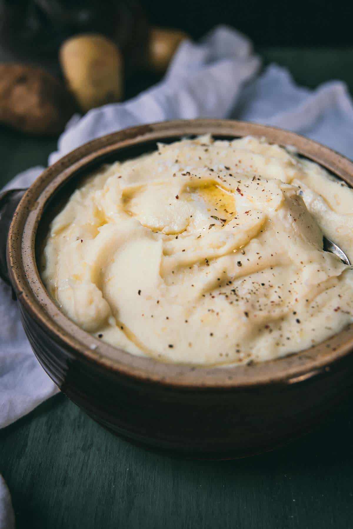 side angle of mashed potatoes in a ceramic crock