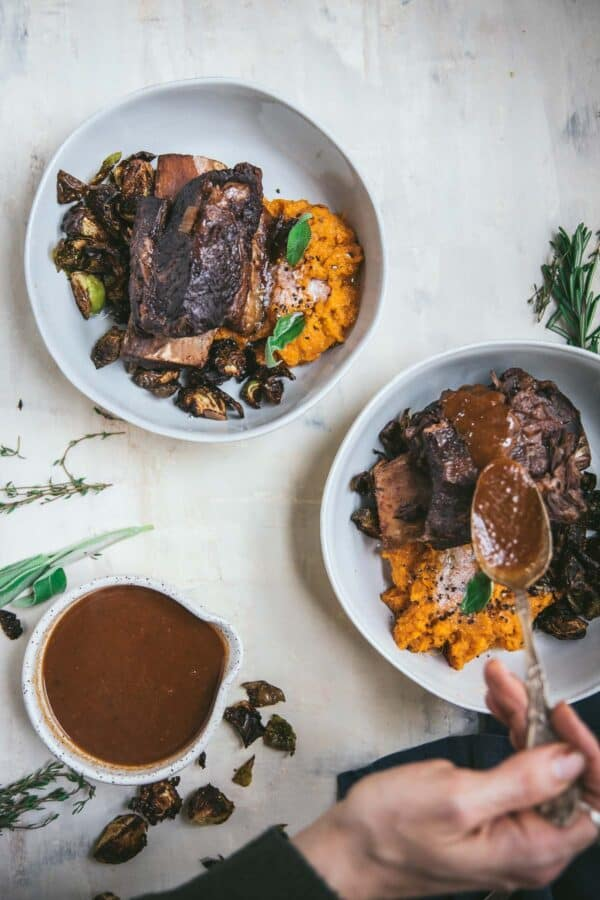 spooning sauce over short ribs in bowls