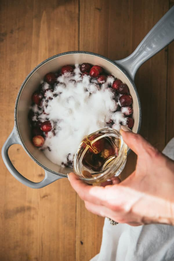 pouring bourbon into a pian with cranberries and sugar