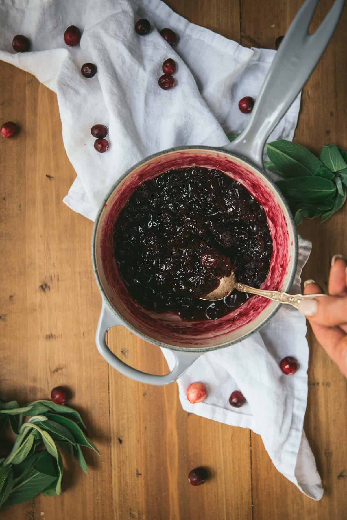 spooning cranberry sauce out of a pan