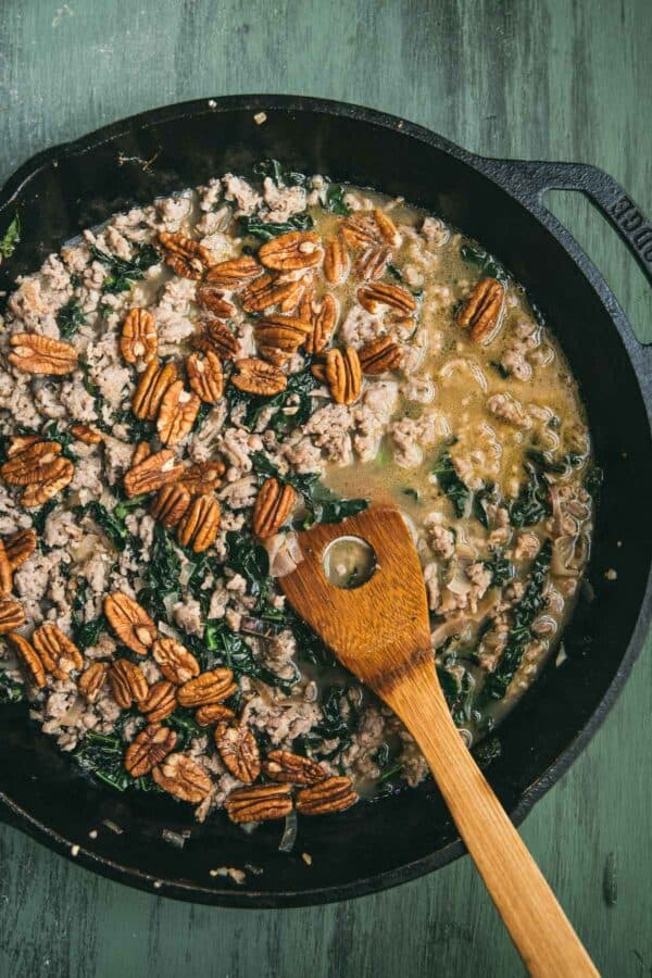 simmered sausage, kale, pecans and chicken stock in a skillet