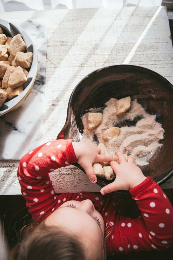 little kid putting sugared biscuits in a pan