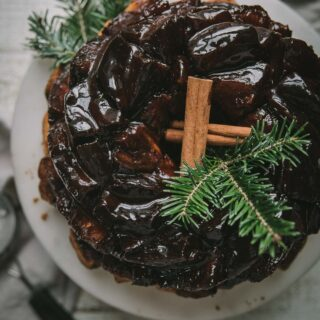 overhead of gooey monkey bread on a cake stand with cinnamon sticks and tree sprigs