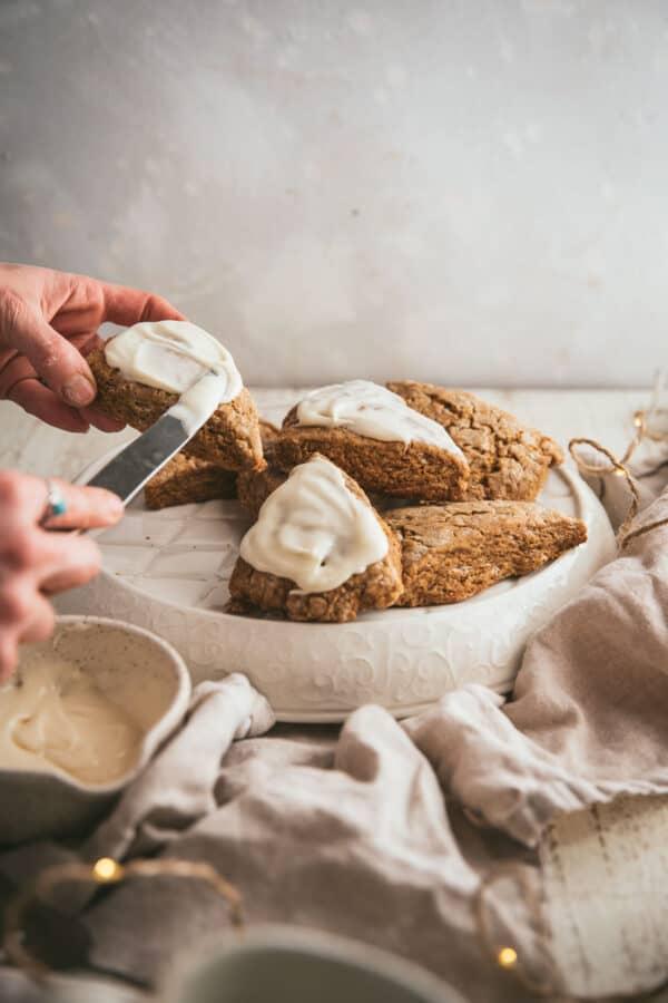 frosting scones over a platter