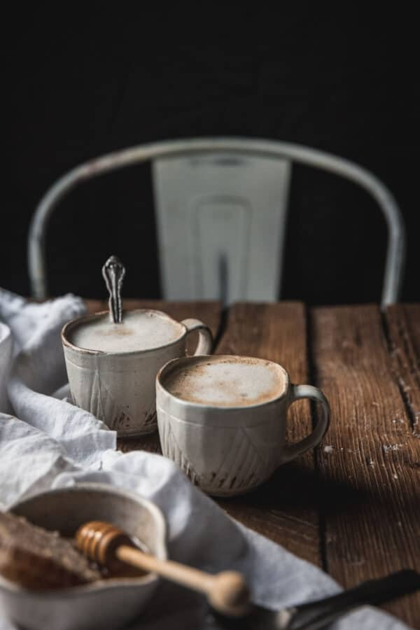 two lattes on a distressed wood table with napkins and honey