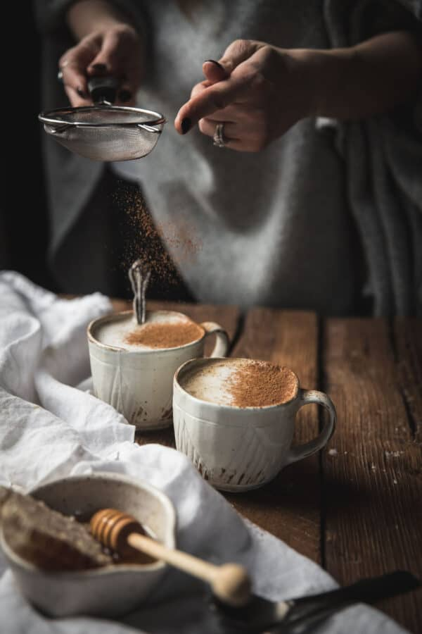 dusting cinnamon over oat milk lattes