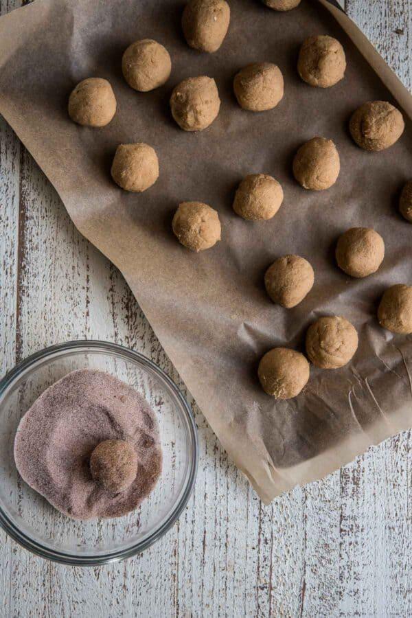 rolling cookies through cinnamon sugar