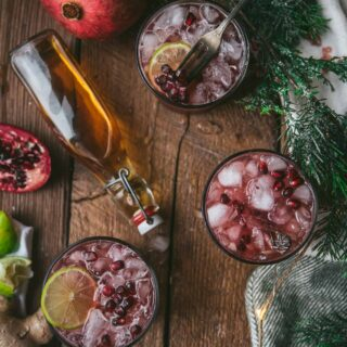 overhead of three pomegranate cocktails and bottle of bourbon on would background