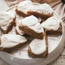 gingerbread scones with cream cheese frosting on a platter