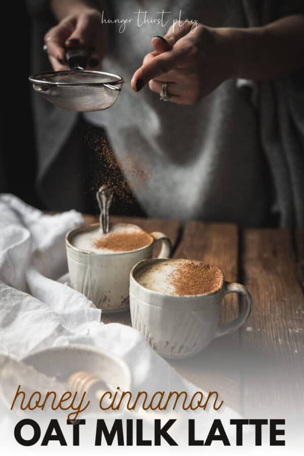 dusting cinnamon over foamy topped lattes