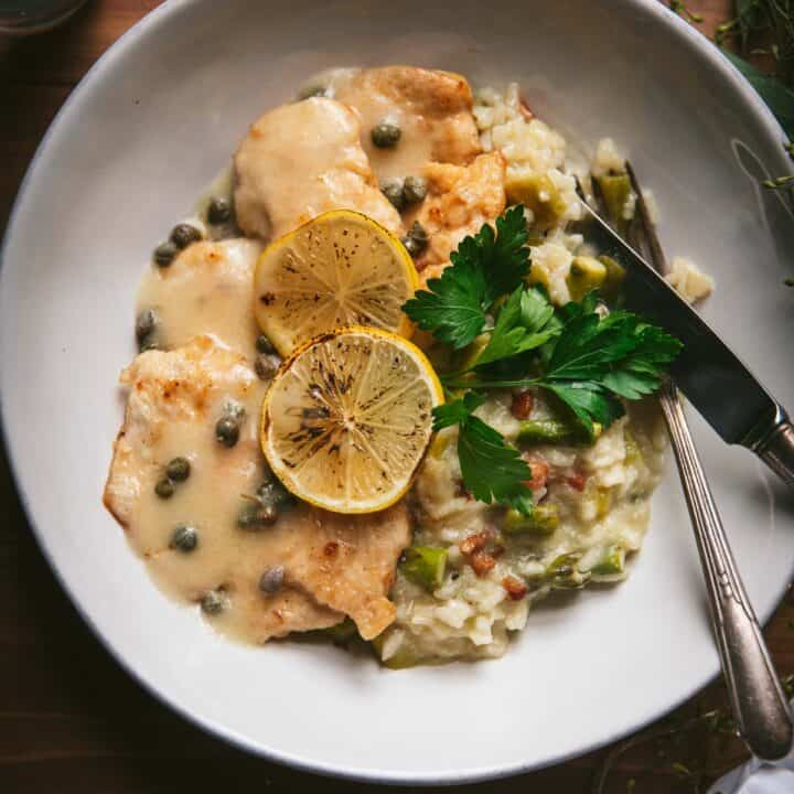 chicken with lemon and caper sauce in a plate over creamy asparagus risotto
