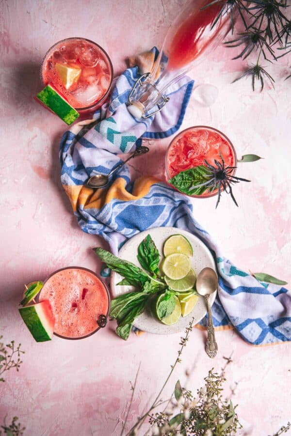overhead of watermelon soda in classes on pink background with blue napkin