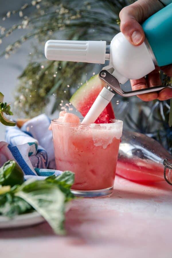 splashing homemade soda into a glass with ice