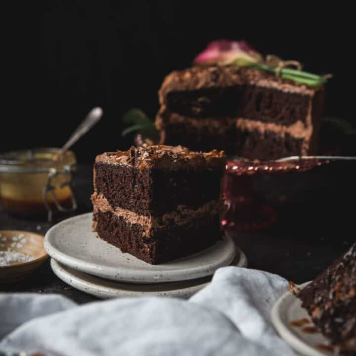 slice of chocolate layer cake on a plate with the cake in the background