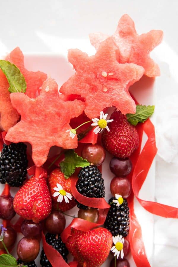 close up of star cut watermelon pieces on top of fruit wands