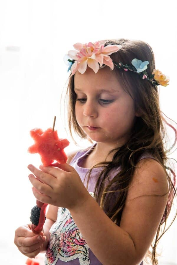 little girl with skewer of fruit