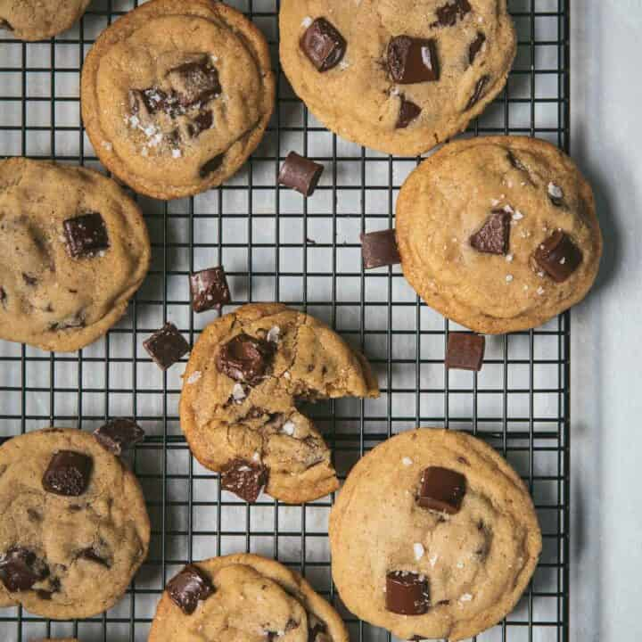 overhead of chocolate chip cookies on a baking rack with sea salt flakes in a bowl
