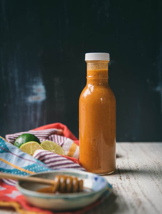 chipotle dressing in a bottle with blue background