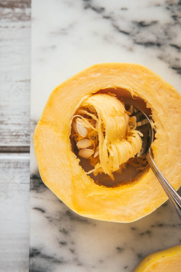 scooping out the seeds of a spaghetti squash