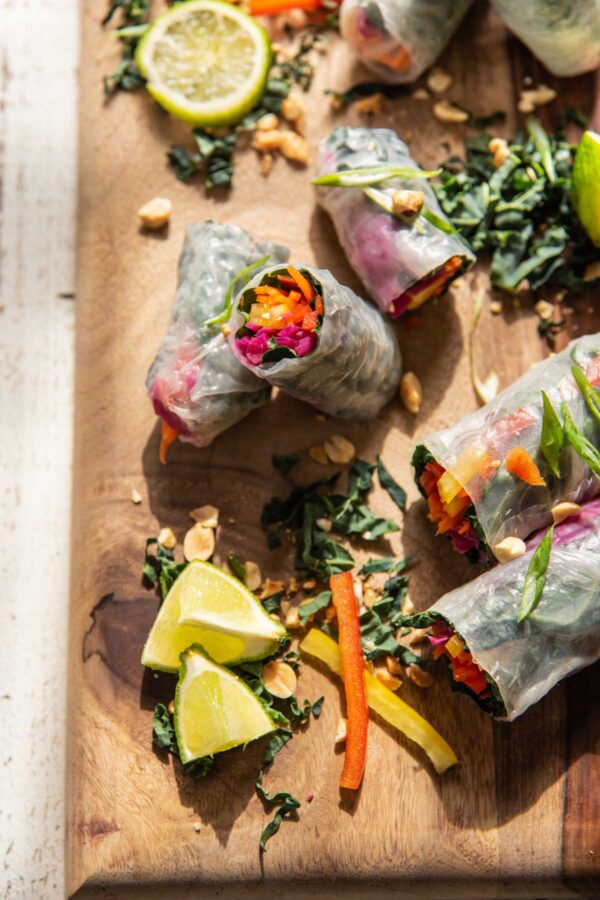 rainbow stuffed rice paper wrapped rolls on a wooden board