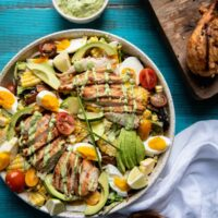 overhead image of cobb salad topped with grilled chicken and greed goddess drizzle