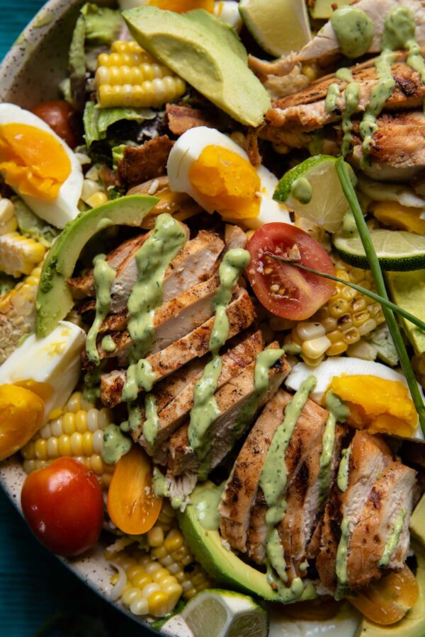 close up of salad with avocado, chicken, eggs, cherry tomatoes