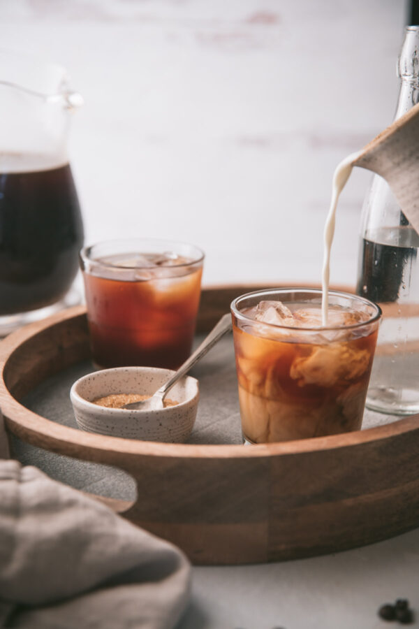 milk pouring into glasses of cold brew coffee
