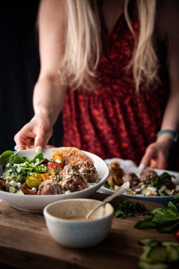 hands grabbing bowls with mediterranean quinoa bowl ingredients