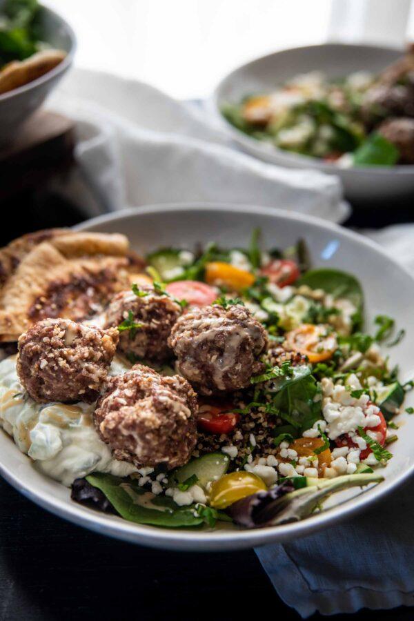 backlit bowl of quinoa, tomatoes, cucumbers, feta, and meatballs