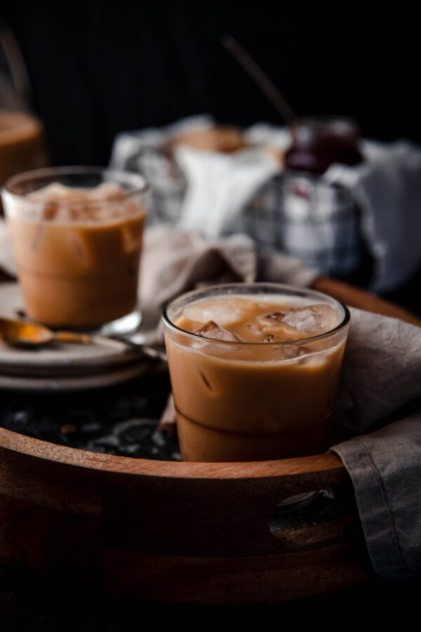 close up of coffee mixed with condensed milk in a glass with ice