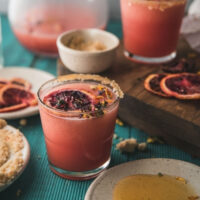 side angle of frozen blood orange margarita in a glass with dried flower garnish