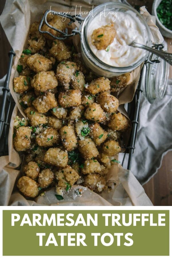 overhead of tater tots in parchment lined basket with garlic aioli