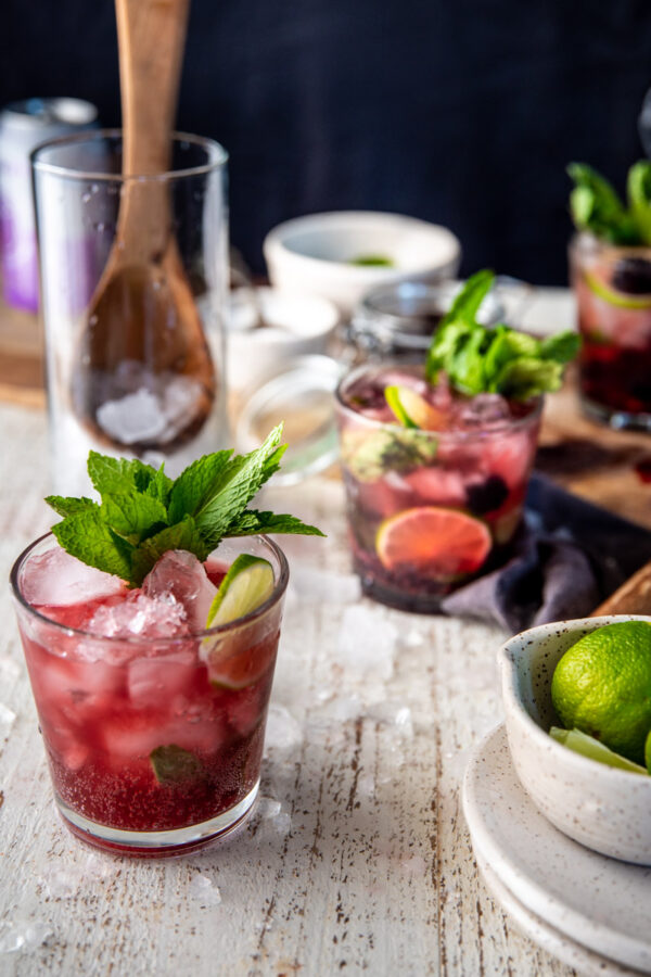 side angle of blackberry mojitos in glasses with mint garnishes