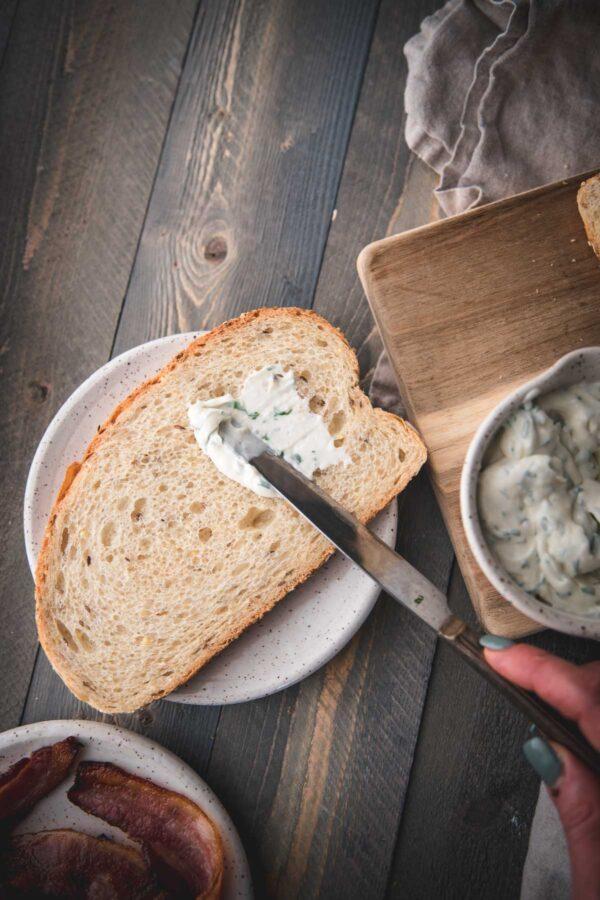spreading garlic basil aioli on bread