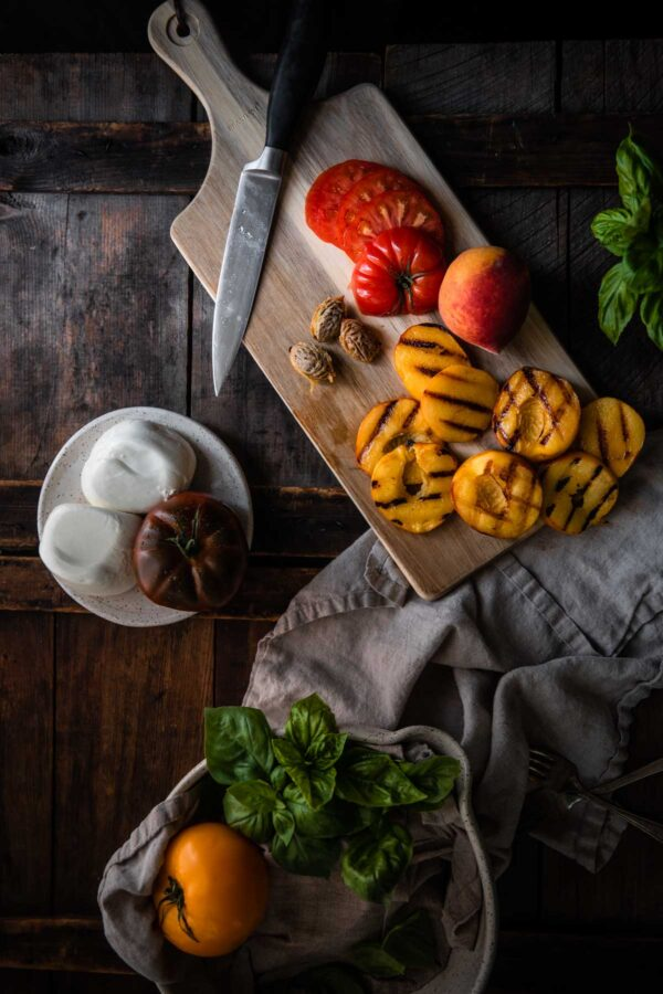 grilled peaches on a cutting board with tomatoes and burrata