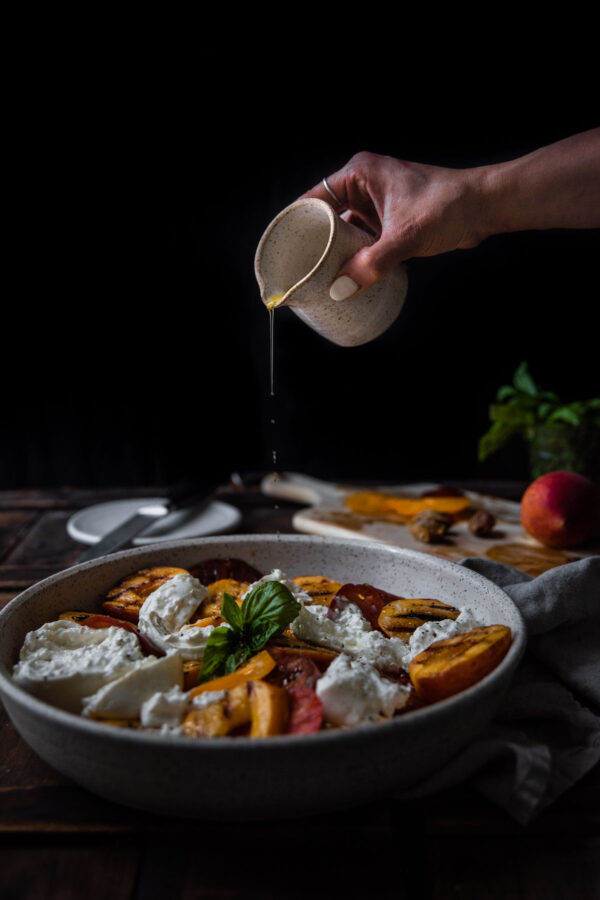 drizzling olive oil over caprese salad