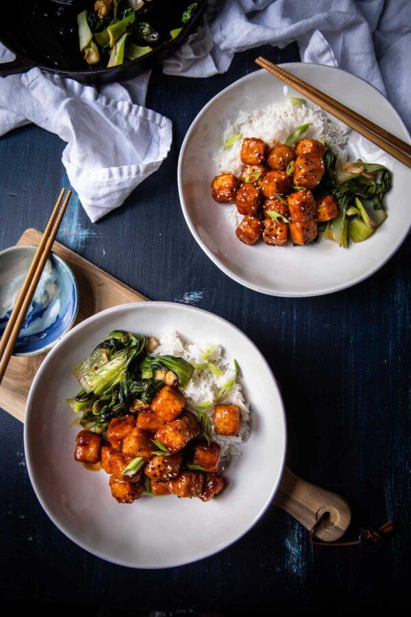 overhead of crispy tofu with sauteed bok choy and coconut rice on plates
