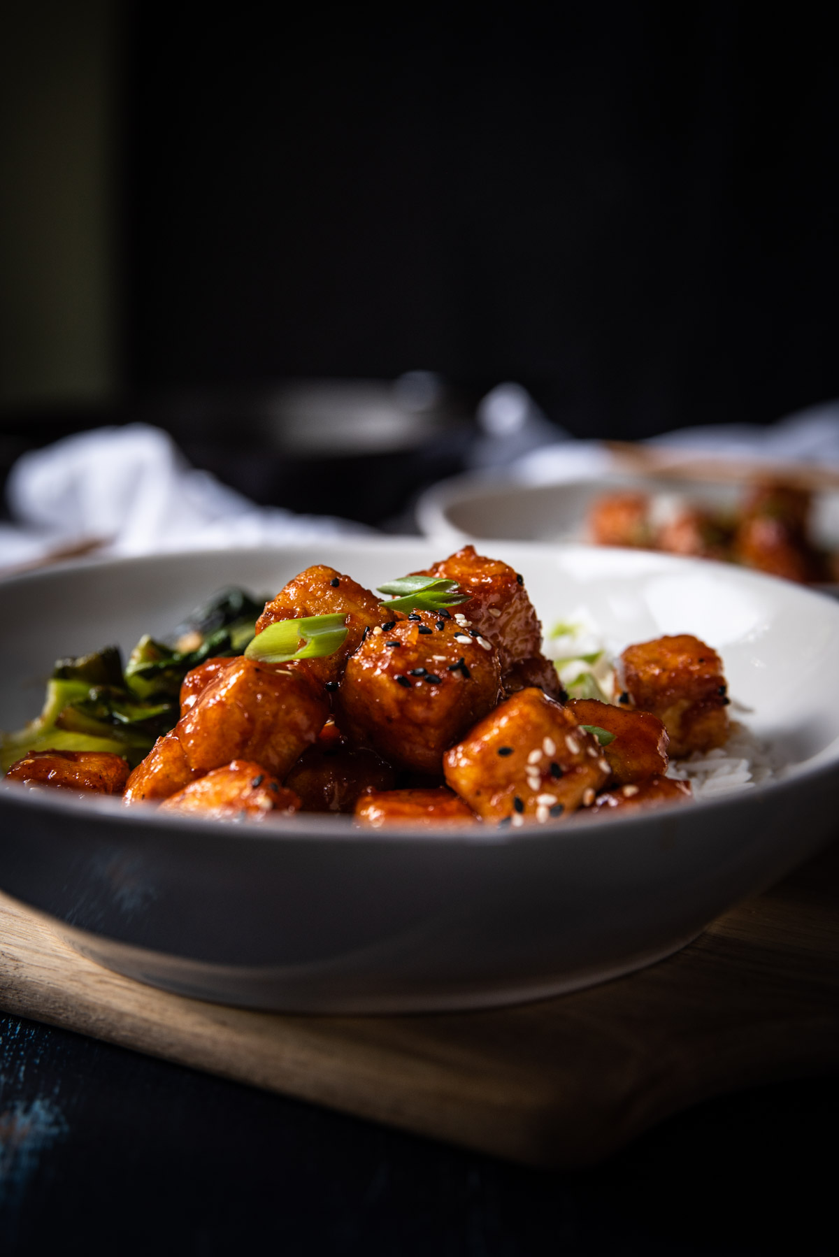 side angle of fried tofu in a bowl with spicy korean sauce