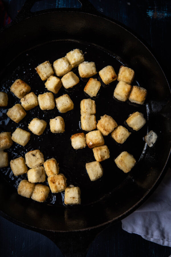 fried pieces of tofu in a cast iron pan