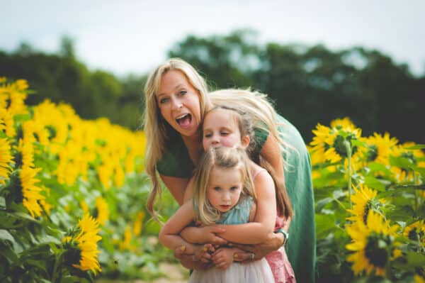 mom and two kids in a sunflower field
