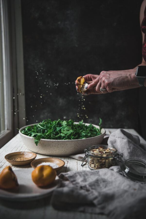 squeezing grilled lemon over arugula greens