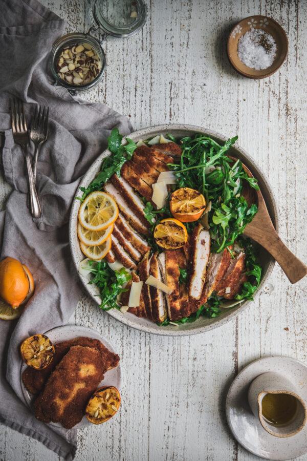 overhead photo of chicken milanese sliced over arugula salad