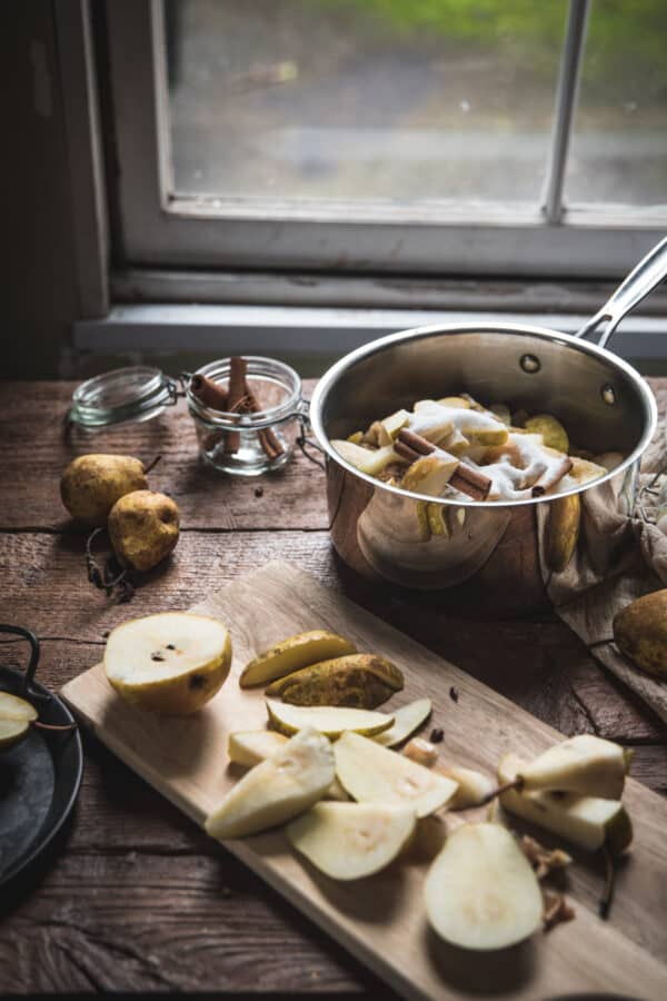 side angle of pan full of sugar, pears, and cinnamon sticks