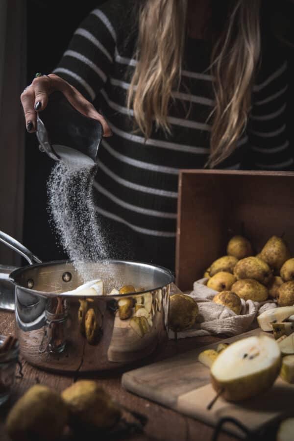 sprinkling sugar in a pan of pears