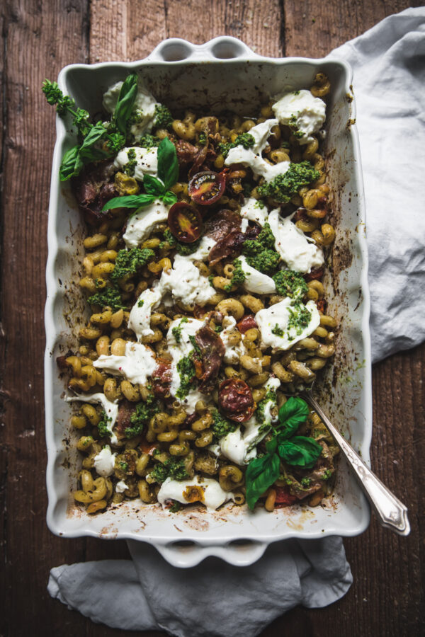 overhead of cooked pesto pasta in one pan with a spoon
