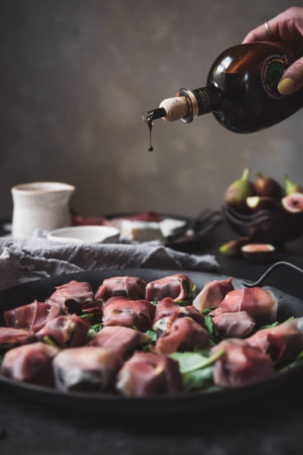 drizzling balsamic vinegar over figs