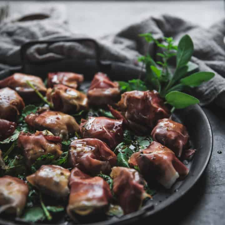 side angle of fresh figs stuffed with gorgonzola and wrapped with prosciutto